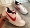 Кроссовки белые с красными вставками.